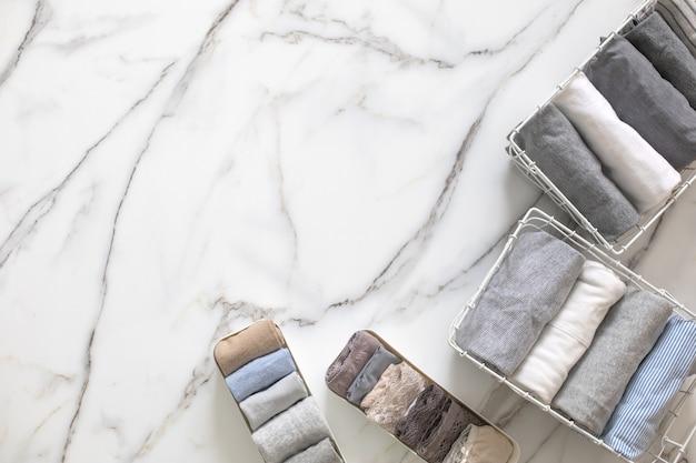 Аккуратно сложенное нижнее белье в разделителе ящика органайзера на белом мраморе
