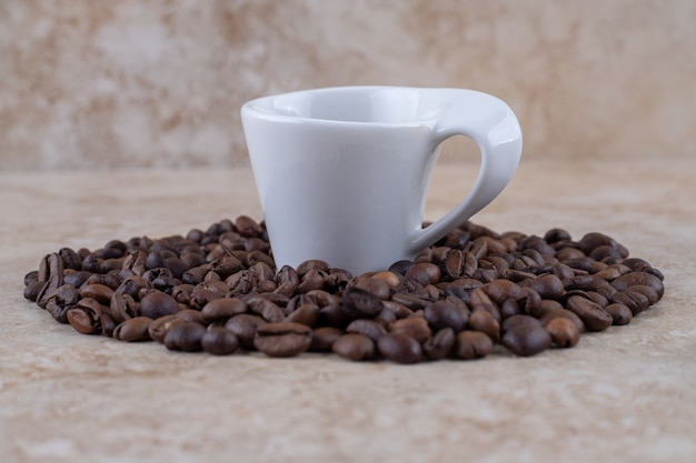 Mucchio ordinatamente organizzato del chicco di caffè che circonda una tazza di caffè