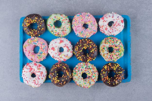 Аккуратно уложенные пончики на блюде на мраморной поверхности