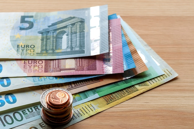 Neatly arranged stack of euro banknotes, currency bills worth ten, twenty, one and two hundred euro and different metal coins. money, busyness and finances, successful investment concept.