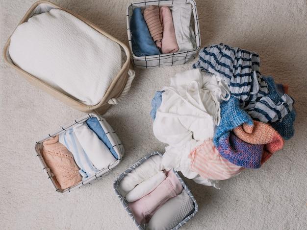 열린 주최자 상자, 위쪽 보기에 깔끔하게 접힌 옷. 청소 방법