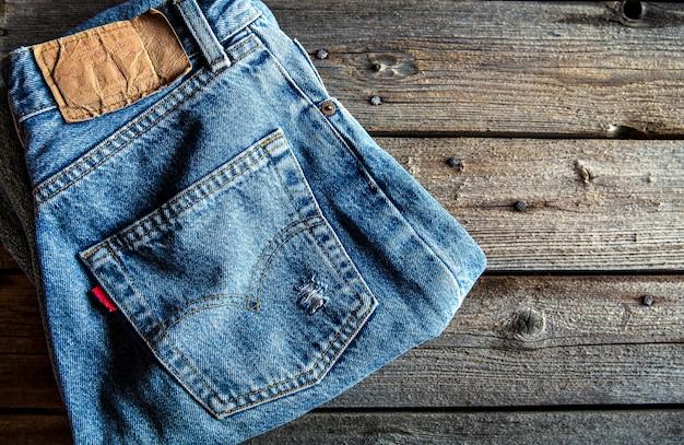 木製の背景にきちんと折りたたまれたジーンズ。服、ファッション、スタイル、ライフスタイル