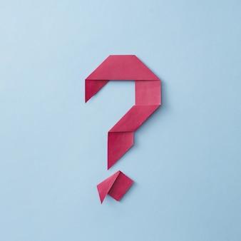 Аккуратно сложенный знак вопроса из красной бумаги оригами на синем фоне для концептуальных тем