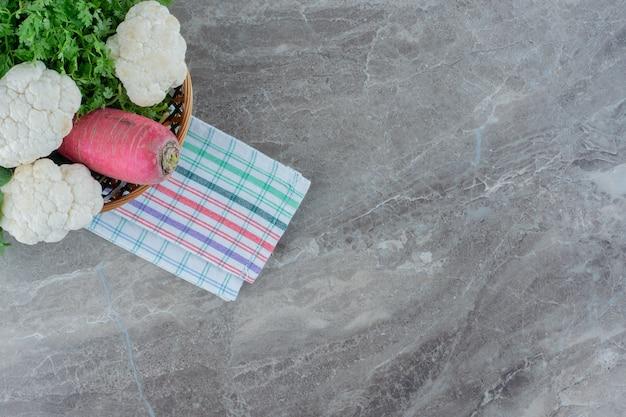 Asciugamano ben piegato sotto un cesto di pezzi di cavolfiore, un fascio di prezzemolo e una rapa su marmo.