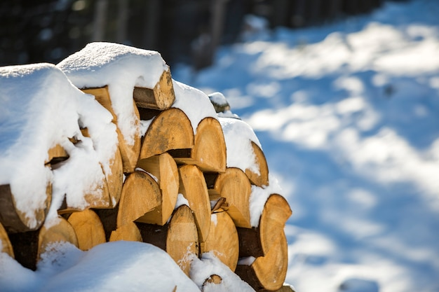 Neatly piled stack of chopped dry trunks wood covered with snow outdoors on bright cold winter sunny day, abstract background, fire wood logs prepared for winter, ready for burning.