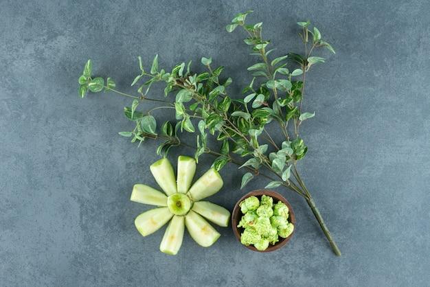 대리석 배경에 장식용 식물과 작은 팝콘 캔디 한 그릇으로 배열된 깔끔하게 썬 사과. 고품질 사진