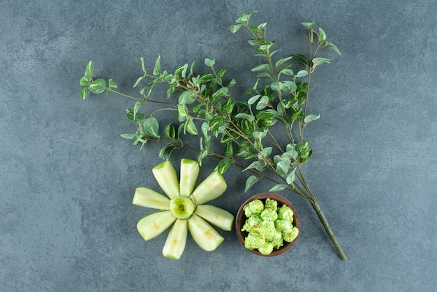 Mela affettata ordinatamente disposta con una pianta decorativa e una piccola ciotola di caramelle popcorn su sfondo marmo. foto di alta qualità