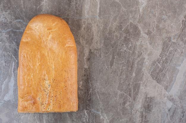 Аккуратно нарезанная полбуханка хлеба тандури на мраморе.