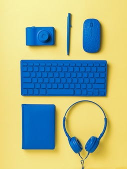 Neatly stacked blue workplace accessories on a yellow surface. stylish accessories for business and freelancing. flat lay.