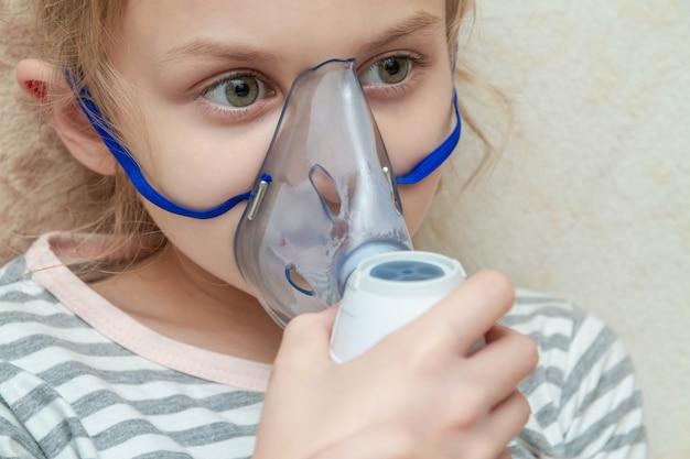 Маленькая девочка делая ингаляцию с nebulizer дома. маленькая девочка с ингалятором. макрофотография, выборочный фокус