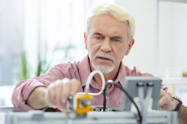 必要な調整。オフィスで働いている間に3dプリンターの設定を変更する魅力的な年配の男性のクローズアップ