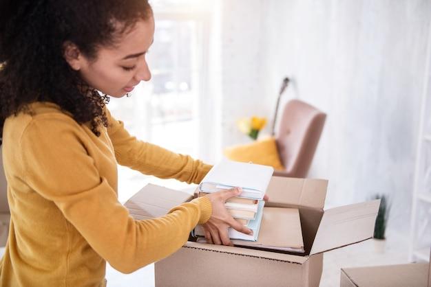 必要な本。古いアパートから移動する準備をしながら、本の山を箱に収める魅力的な縮れ毛の少女