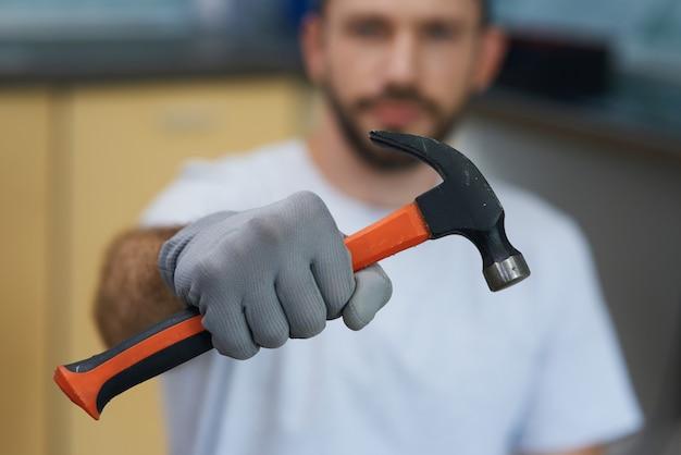Необходимый ручной инструмент крупным планом выстрел руки молодого ремонтника, держащего молоток