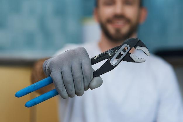 필요한 손 도구는 파이프 렌치를 들고 있는 젊은 수리공의 손을 클로즈업합니다.