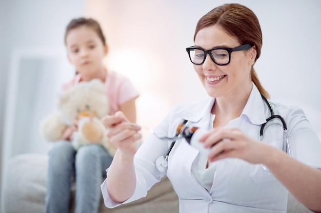 Необходимые лекарства. веселая веселая женщина-врач наливает лекарство для помощи девушке, позируя на размытом фоне