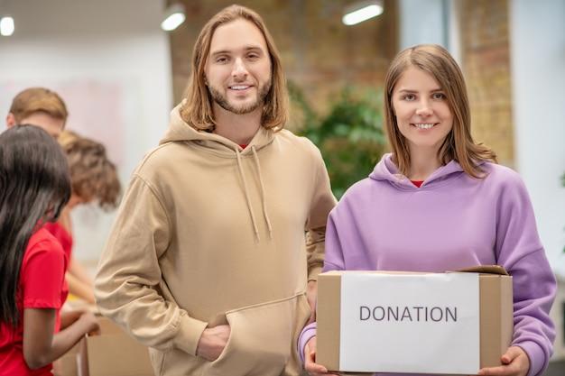 필요한 지원. 복지 센터에 서서 기부금 상자를받은 젊은 행복 감사 남자와 여자