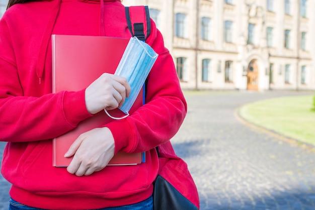 의료용 마스크를 착용하고 사회적 거리 개념을 유지해야 합니다. 카피북과 얼굴 마스크를 들고 캐주얼한 빨간 운동복을 입은 어린 십대 소녀의 클로즈업 사진