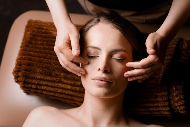 스파에서 목과 얼굴 마사지. 안마사는 매력적인 여성 모델을 위해 얼굴 미용 치료를하고 있습니다. 기분 전환.