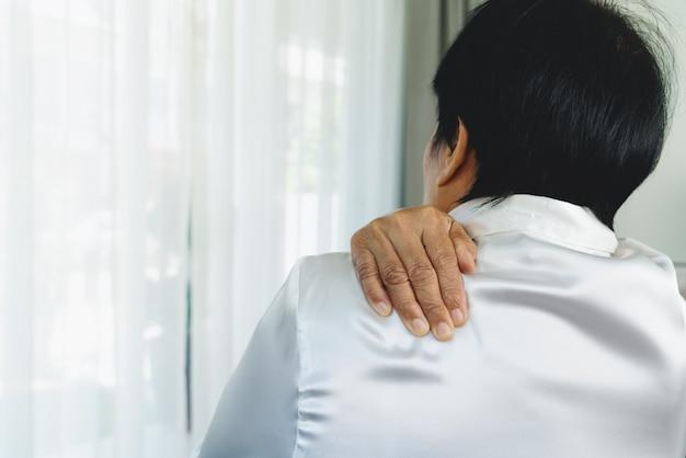 首と肩の痛み、首と肩の怪我に苦しんでいる老婆、健康問題の概念