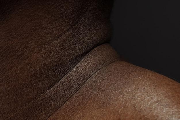 首。人間の肌の詳細な質感。若いアフリカ系アメリカ人の男性の体のクローズアップショット。スキンケア、ボディケア、ヘルスケア、衛生、医学の概念。美しさと手入れの行き届いたように見えます。皮膚科。