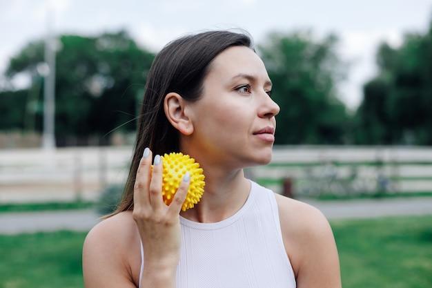 공원에서 근육통 완화 및 근막 이완을위한 뾰족한 노란색 마사지 볼을 사용한 목 마사지 ...