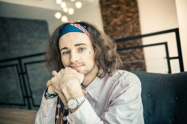 Гриф гитары. улыбающийся красивый молодой художник с ярко-голубыми глазами, положив подбородок на скрещенные руки