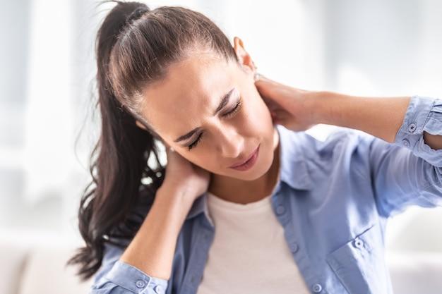 痛みを伴う表情を持つ自宅の女性の首の痛み。