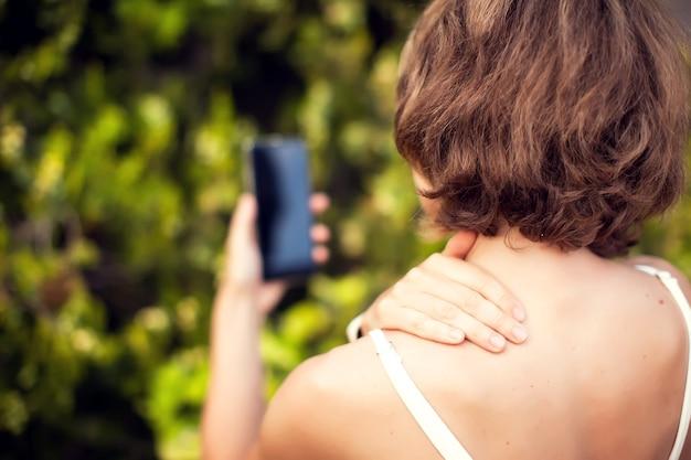 Боль в шее при использовании смартфона на открытом воздухе. концепция здравоохранения, образа жизни и технологий