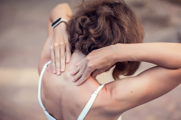 Neck pain. woman feeling neck or shoulder ache outdoor. healthcare and lifestyle concept