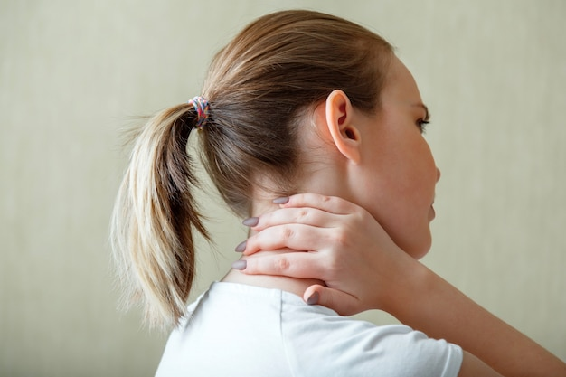 목 어깨 통증, 경추. 여자는 손으로 목 통증 경추 근육 경련을 보유하고 있습니다. 젊은 여성의 근골격계 질환. 건강 관리 및 의료 개념.