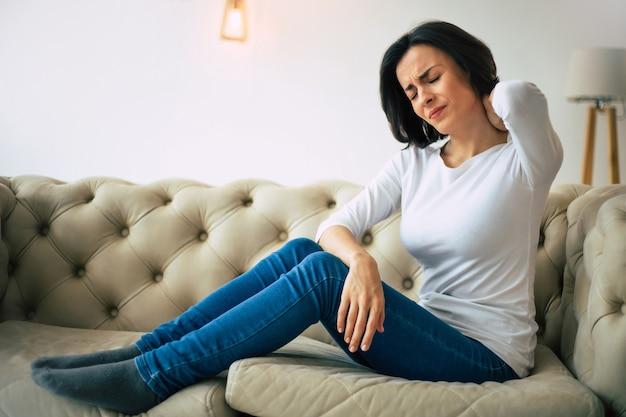 首の緊張の症状。若い女性は自宅のソファに座って首の緊張に苦しんでいる間、首の後ろに触れています。
