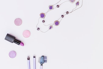 Necklace; eye shadow; lipstick and makeup brush on white background