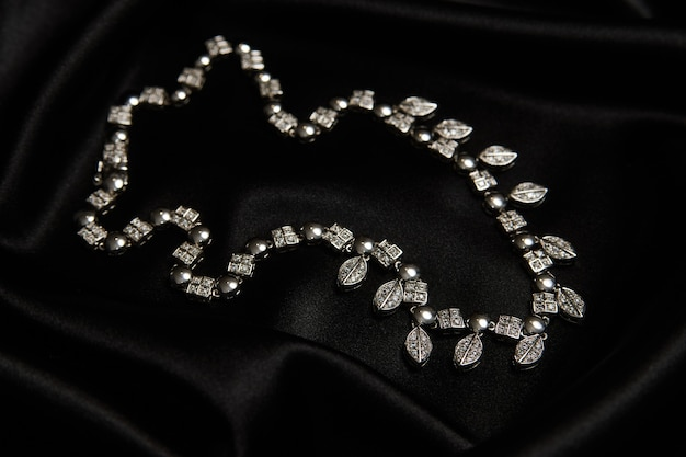Necklace with diamonds on black background with copy space. women's platinum necklace with a precious gemstones, close-up. elegant female jewelry
