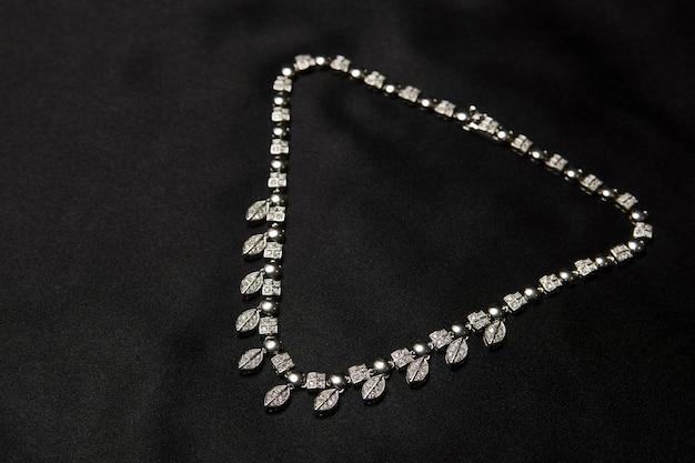 복사 공간이 있는 검은색 바탕에 다이아몬드가 달린 목걸이. 귀한 보석으로 장식된 여성용 플래티넘 목걸이, 클로즈업. 우아한 여성 보석