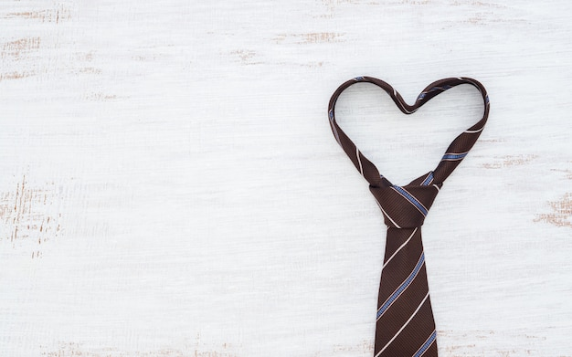 Necktie in heart shape on grunge white wooden table background.