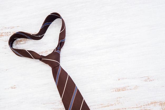 Necktie in heart shape on grunge white wooden table background.
