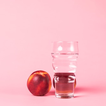 Nectarine and water on pink background