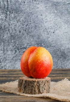Nectarine with piece of sack, wood timber side view on wooden and grungy wall