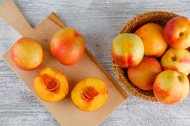 Nectarines in a basket on grungy and cutting board table. flat lay.