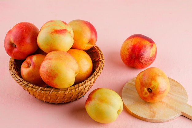 Nectarines in a basket on pink and cutting board table. high angle view.