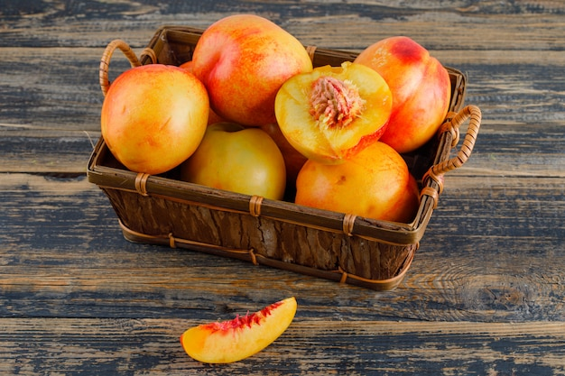 Nectarines in a basket on wooden table, high angle view.