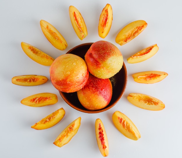 Nectarines in a bowl flat lay on a white surface