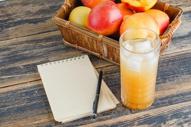 木製の壁にノート、ペン、ジュースの高角度のビューが付いているバスケットのネクタリン