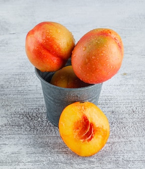 Nectarines in a mini bucket on grungy grey surface, high angle view.