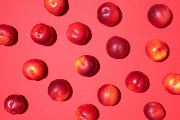 Nectarines pattern on red background