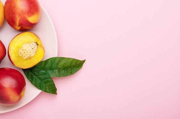 Нектарины персиков, нарезанные дольками с листьями на розовой тарелке на ярком фоне. органические летние фрукты, еда здорового образа жизни, вид сверху, копия пространства.
