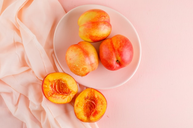 Nectarines in a plate on pink and textile surface. flat lay.