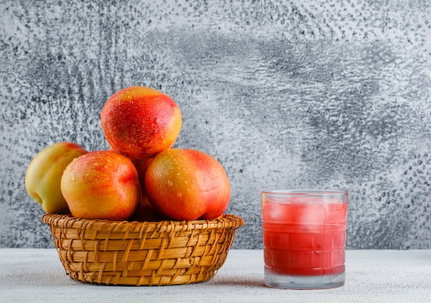 Nectarines with juice in a basket on grungy and white background, side view.