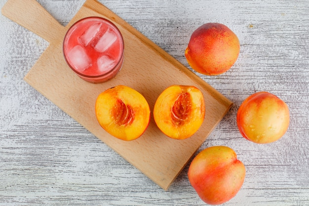 Nectarines with juice on grungy and cutting board table, flat lay.