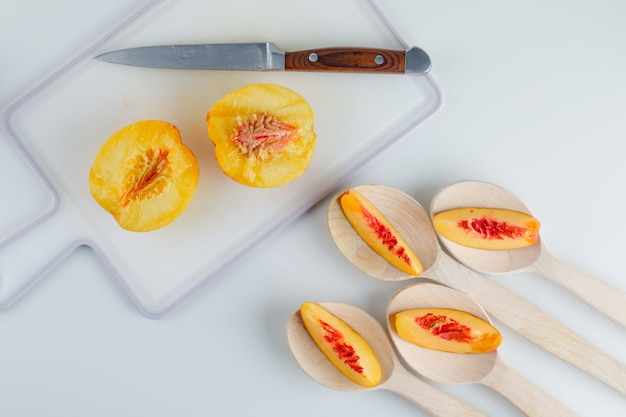 Нектарины с ножом в деревянные ложки на белом и разделочная доска таблицы, плоская планировка.